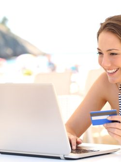 Woman buying online on vacations with a laptop and a credit card in a snack bar on the beach